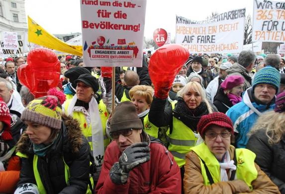 Протестующие работники общественных служб с плакатами во время протестов 18 декабря 2013