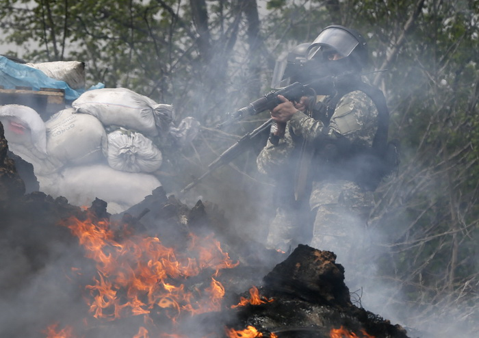 Ukrainian security force officers walk past a checkpoint set on fire and left by pro-Russian separatists near Slaviansk