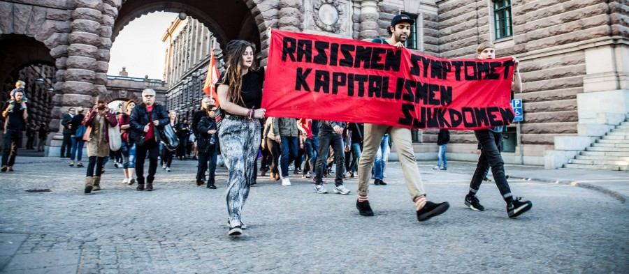 """Фото с антифашистской акции в Стокгольме, середина сентября 2014: """"Расизм - симптом, капитализм - болезнь""""."""