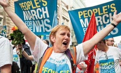 Женщина, одетая в майку «Народный Марш за государственную систему здравоохранения», машет руками и скандирует лозунги.
