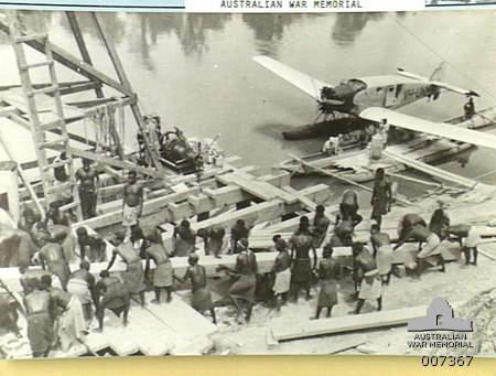 Май 1941 г. Островитяне сооружают пристань для австралийских войск. На заднем плане – самолет Junkers, который использовался для доставки грузов в отдаленные районы.