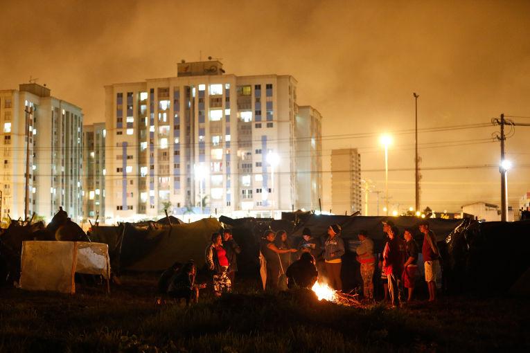 «Бездомные рабочие» греются у костра в лагере в городе Сейландия. В дождливые ночи вокруг костров здесь собирается около трех тысяч человек.