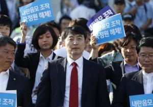 Lee Seok-Ki, lawmaker of opposition United Progressive Party, and other lawmakers of the party leave the main building of parliament in Seoul