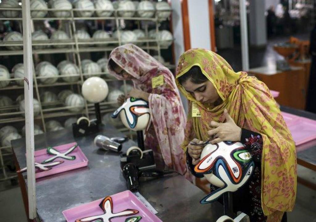 Пакистанские женщины делают мячи к чемпионату мира в Бразилии