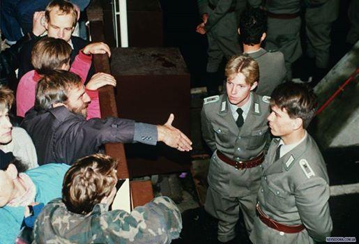 """""""Пограничные полицейские Восточной Германии отказываются от рукопожатия восточного берлинца, стоя на восточной стороне рядом с КПП Чарли 10 ноября 1989 года, после открытия границы. К предателям - никакого уважения быть не может""""."""