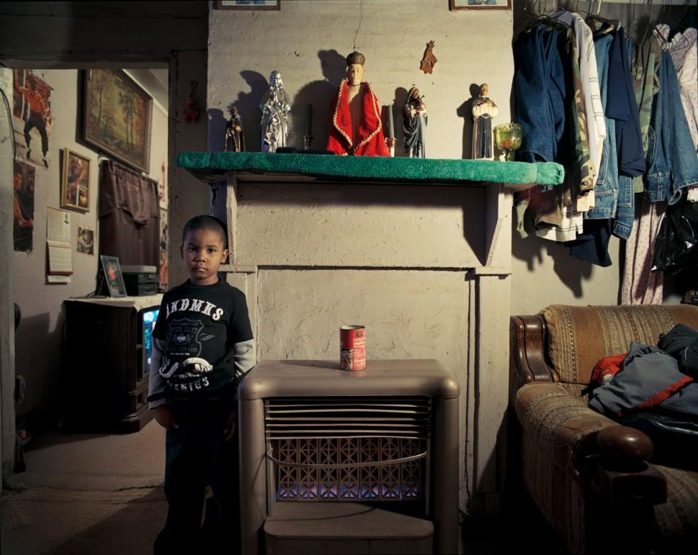 Квинтавиус Скотт (5 лет) в спальне своей прабабушки Барбары Келли в Афинах, Джорджия. Его отец, Квинтон Скотт, зарабатывает $8.25 в час и посещает школу, чтобы получить разрешение на коммерческую деятельность. Квинтавиус занимается по федеральной дошкольной программе для малоимущих, и его родители даже будучи разведенными, вместе заботятся о его будущем.