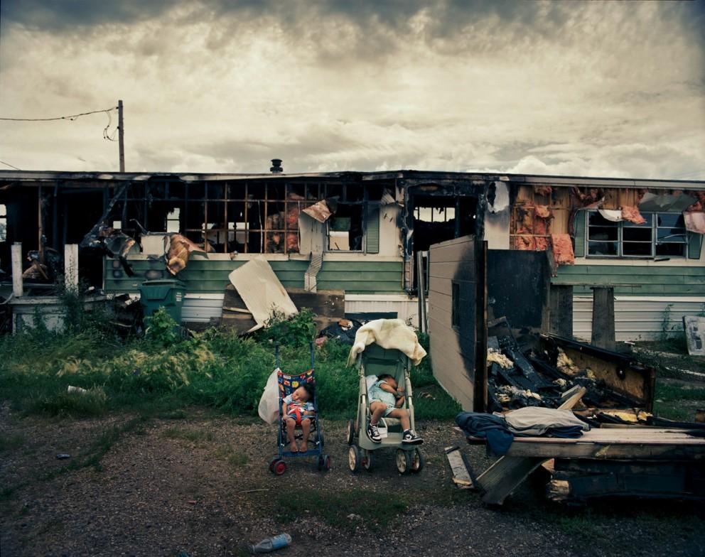 Две внучки Адель Уайт Дог Джонсон спят в колясках рядом со сгоревшим домом на колесах в Игл Бьютт. 45-летняя Адель жаловалась на электропроводку всего за неделю до пожара. В результате никто не пострадал, но семья потеряла все свое имущество, включая и недавно купленный компьютер. Адель, у которой сгорает из-за проводки уже второй трейлер, работает посудомойкой.
