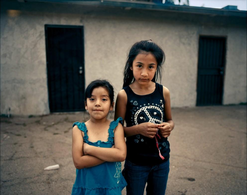 Подруги Жасмин (6 лет) и Эми (8 лет) рядом с мотелем для кочующих сельхоз работников в Фрезо, Калифорния. Мать Эми зарабатывает на ферме 8 долларов в час.