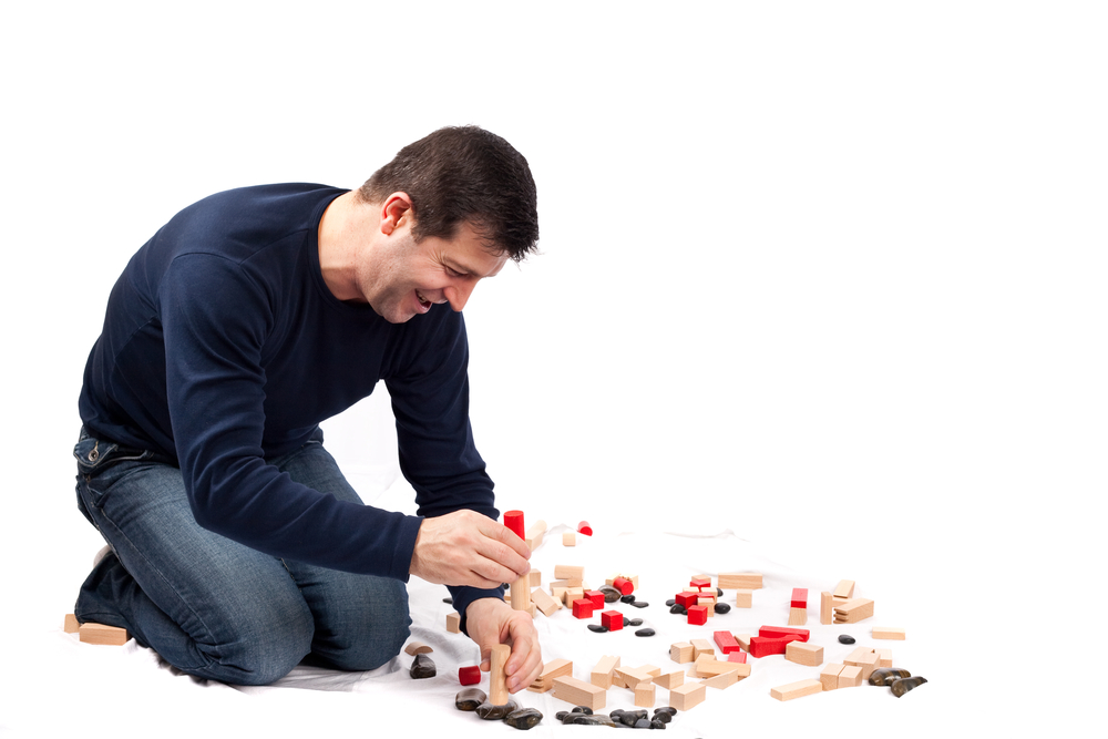 Man playing with wooden construction set
