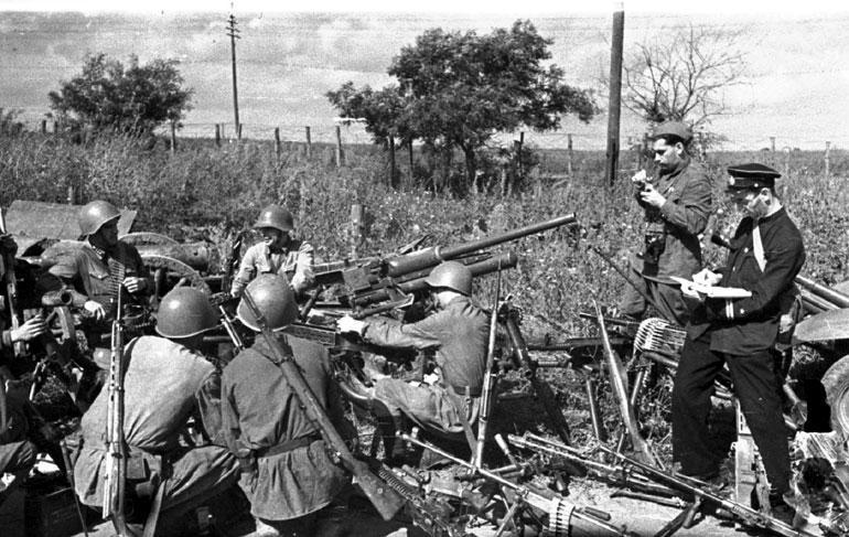 Защитники Одессы осматривают трофейное оружие.