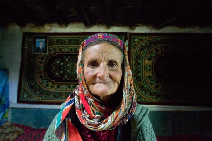 Жительница горного кишлака на Памире. На стене слева — портрет имама исмаилитов Ага-Хана IV. Фотография автора.