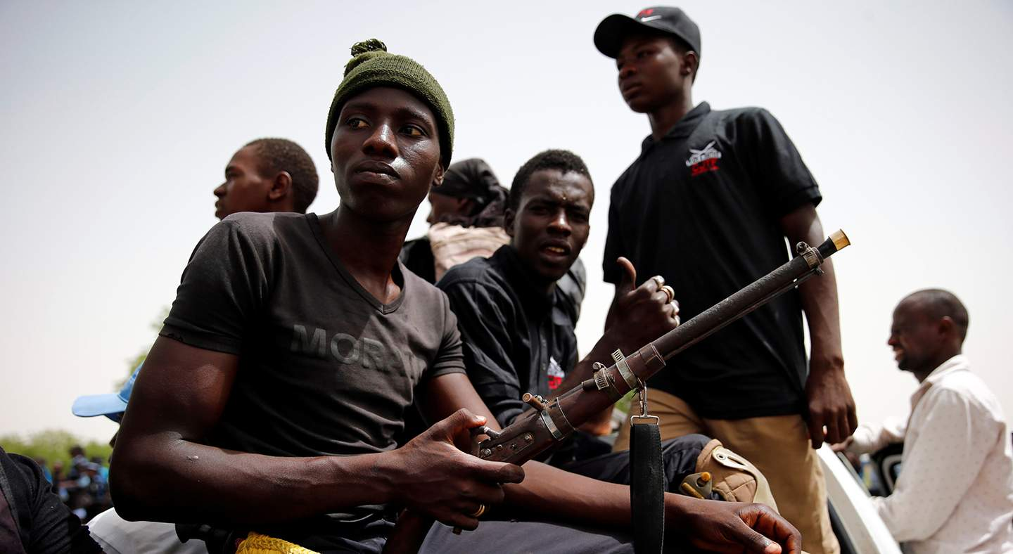 Members of the local militia, otherwise known as CJTF, sit in the back of a truck during a patrol in Maiduguri